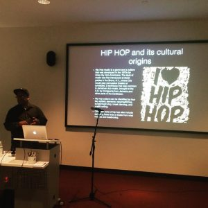 "Alonzo Lee in front of a slide that says ""I heart Hip Hop"""